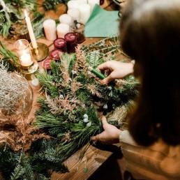 Workshop Teilnehmerin bindet eigenen Adventskranz bei Ganz Unverblümt in Straubing