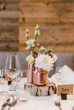Tischschmuck mit Blumen in Pastelltönen und kupferfarbenen Elementen als Tischschmuck von Hochzeitsfloristin Ganz Unverblümt
