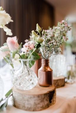 Kristallvasen, kupferfarbene Gläser und Baumscheiben mit pastellfarbenen Blumen von Ganz Unverblümt Bayerischer Wald