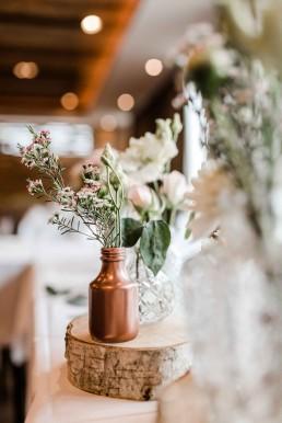 Kupferfarbene Vasen und Baumscheiben mit pastellfarbenen Blumen auf Vintage-Hochzeit im Toni´s in Straubing