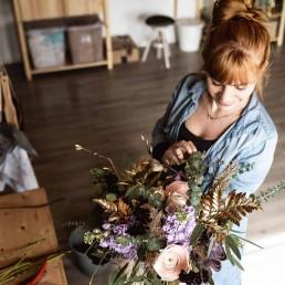Floristin Franzi bei der Arbeit mit Brautstrauß in ihrem Werkraum in Steinach bei Straubing