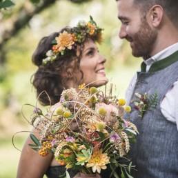 Brautpaar in Tracht mit natürlich gebundenem Blumenschmuck von Ganz Unverblümt Regensburg