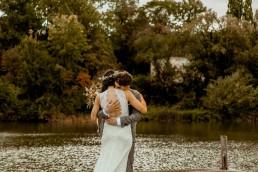 Brautpaar umarmt sich bei Boho-Hochzeit mit herbstlicher Blumendeko von Ganz Unverblümt Straubing