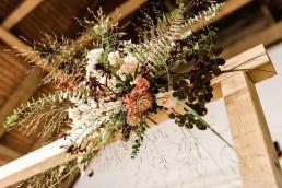 Herbstlicher Blumenschmuck mit Eucalytpus und Gräsern an Traubogen auf Boho Hochzeit in Niederbayern