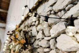 Lichterketten und natürlicher Blumenschmuck vor Wand über dem Buffet auf freier Trauung in Gut Haggn Neukirchen