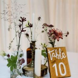 Natürlicher Tischschmuck in Herbsttönen mit Baumscheiben und Vasen von Dekoverleih mit Herz Steinach
