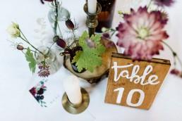 Natürliche Tischdeko mit Apothekerflaschen, goldenen Kerzenständern und Holzschildern von Dekoverleih mit Herz und Ganz Unverblümt Straubing