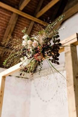 Herbstliches Blumengesteck an Traubogen aus Holz auf freier Trauung im Bayerischen Wald