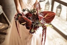 Exotischer Brautstrauß mit roten Anthurien und Akzenten in Blau von Floristmeisterin Franzi Straubing